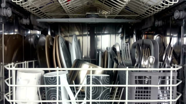 Elevating shot of a dish washer loaded with crockery and cutlery Elevating shot of the inside of a dish washer loaded with crockery and cutlery after a wash washing dishes stock videos & royalty-free footage