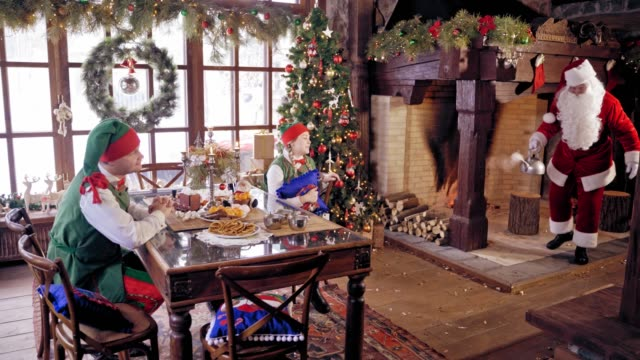 Elves sitting at the table on beautifully decorated background for Christmas.