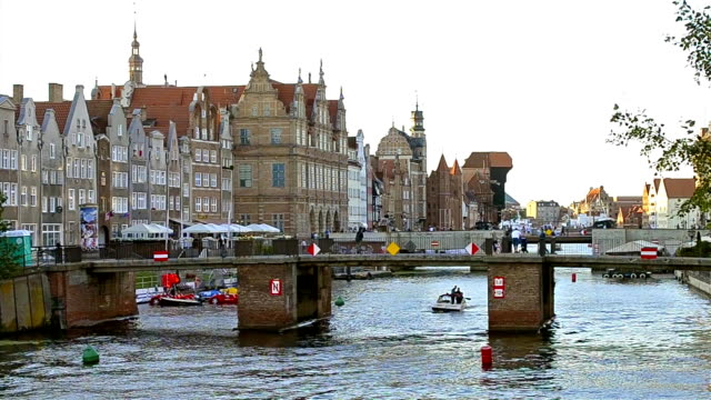 Embankment of Hanseatic port city Gdansk in Poland Gdansk, Poland - July 19, 2017: Pleasure boat rides under bridge over river Stara Motlawa. Embankment of Hanseatic port city Gdansk with coastal buildings in half-timbered style Fachwerk. Tourist walk gdansk stock videos & royalty-free footage