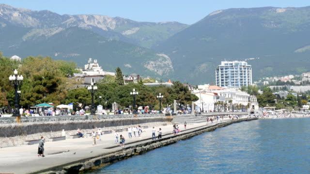 yalta, krim - 1 maj 2018: banvallen av havet staden, där människor går. en havet stad i bergen - walking home sunset street bildbanksvideor och videomaterial från bakom kulisserna