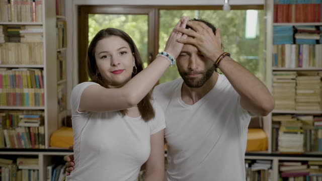 embarrassed millennial man slapping his forehead doing facepalm next his girlfriend happy funny couple having fun - errore video stock e b–roll