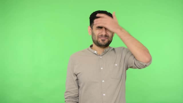 Embarrassed upset brunette man making facepalm gesture and holding hands on head. green background, chroma key