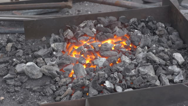 Embers glow in a iron forge. Annealing and heat-treating of iron parts for forging. Embers glow in a iron forge. Annealing and heat-treating of iron parts for forging. Static camera. wrought iron stock videos & royalty-free footage