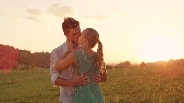 close up: embraced young lovers kiss passionately in the rainy green countryside - data scritta video stock e b–roll