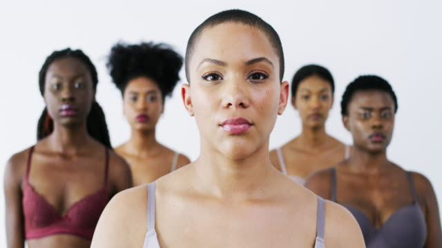 Embracing every shade of beauty 4k video footage of a group of beautiful young women posing against a white background bolos stock videos & royalty-free footage
