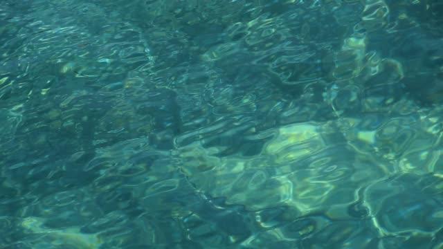 vídeos de stock, filmes e b-roll de ondulações do mar verde esmeralda correndo na superfície da água - esmeralda