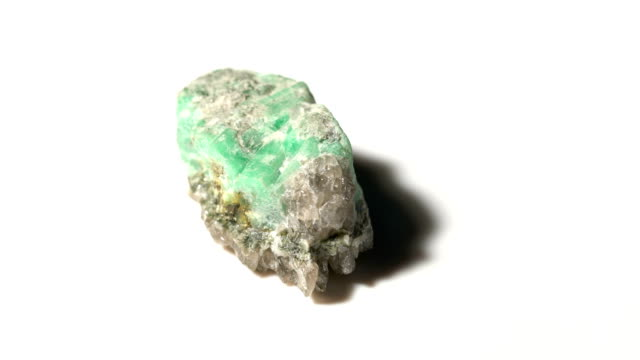 emerald mineral stone sample in rotation with white background