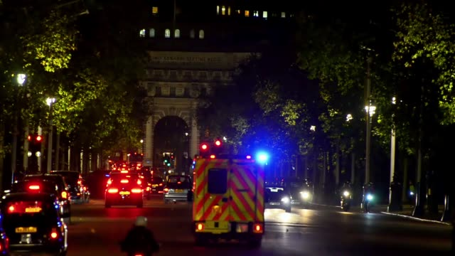 Emergency ambulance crosses Mall road toard Trafalgar square with lights flashing at night video