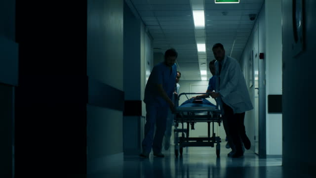 Emergency Department: Doctors, Nurses and Paramedics Push Gurney / Stretcher with Seriously Injured Patient towards the Operating Room. Emergency Department: Doctors, Nurses and Paramedics Push Gurney / Stretcher with Seriously Injured Patient towards the Operating Room. Shot on RED EPIC-W 8K Helium Cinema Camera. stretcher stock videos & royalty-free footage