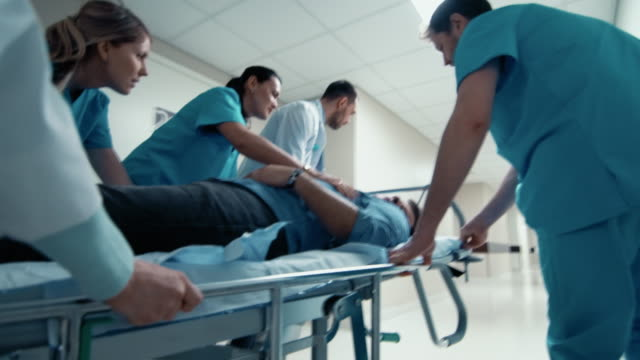 vídeos de stock e filmes b-roll de emergency department: doctors, nurses and paramedics run and push gurney / stretcher with seriously injured patient towards the operating room. bright modern hospital with professional staff saving lives. - medicare