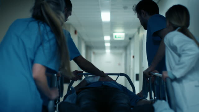 vídeos de stock e filmes b-roll de emergency department: doctors, nurses and surgeons move seriously injured patient lying on a stretcher through hospital corridors. medical staff in a hurry move patient into operating theater. - medicare