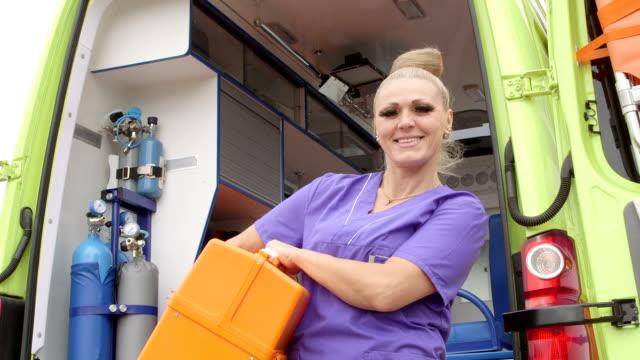 Servicio técnico en urgencias médicas de emergencia médica hembra en frente de ambulancia - vídeo