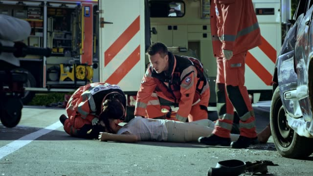 emergency medical service team checking the vital signs of a young woman lying on the ground at the scene of a car crash - paramedic stock videos and b-roll footage