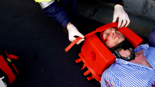 Emergency medical technician protecting the head of his wounded person video