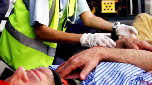 Emergency medical technician taking the pulse of his wounded person Emergency medical technician taking the pulse of his wounded person on the floor stretcher stock videos & royalty-free footage