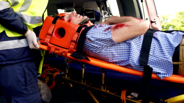 Emergency medical technicians holding a wounded person Emergency medical technicians holding a wounded person on a stretcher stretcher stock videos & royalty-free footage
