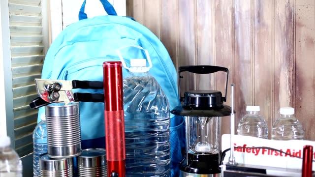 emergency preparedness natural disaster supplies.  water, flashlight, lantern, radio, batteries, first aid kit. - evento catastrofico video stock e b–roll