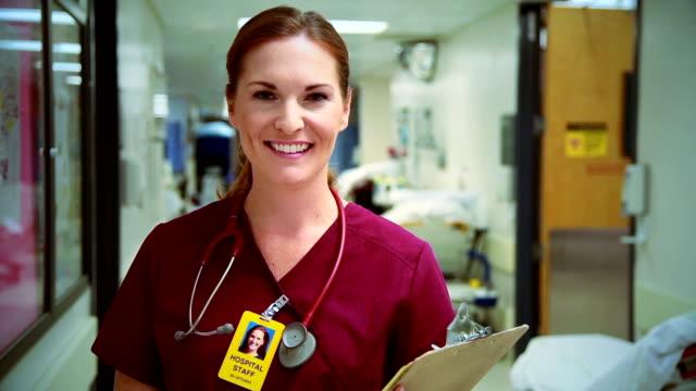 acil servis hemşiresi gülümsüyor - cerrahi önlük stok videoları ve detay görüntü çekimi
