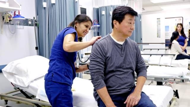 vídeos y material grabado en eventos de stock de el médico de la sala de emergencias escucha los pulmones del paciente masculino - geriatría