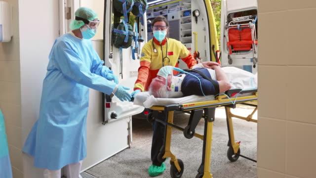 vídeos de stock e filmes b-roll de emergency teams caring for covid-19 patient on stretcher - covid hospital