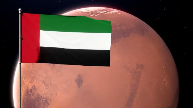 emirates flag waving on the background of the planet mars. united arab emirates - uae flag filmów i materiałów b-roll