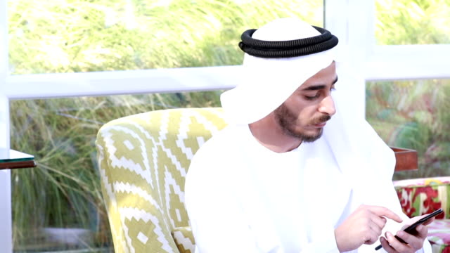Emirati Arab using a Smart Phone at a Cafe - 4k video