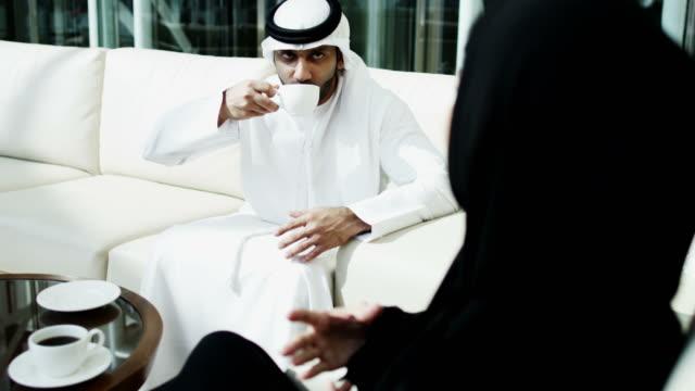 i colleghi di lavoro emiratini incontrano l'atrio dell'hotel del centro del caffè - cultura del medio oriente video stock e b–roll