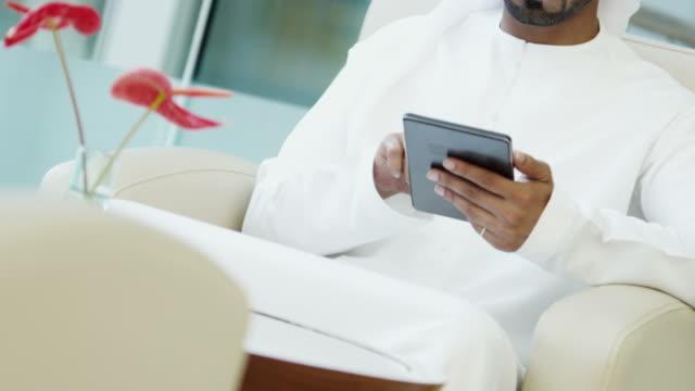 Emirati business executive wearing national dress wireless tablet video
