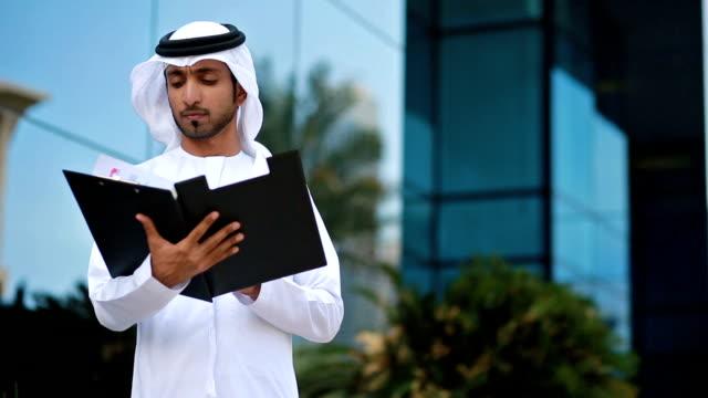 Emirati businessman checking folder documents video