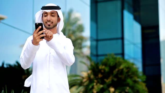 Emirati businessman using phone outdoors video