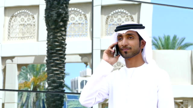 emirati businessman using phone outdoors - oman filmów i materiałów b-roll