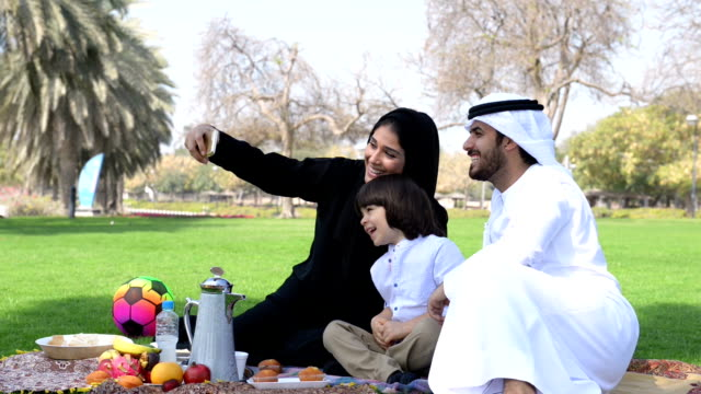 emirati family taking a selfie at picnic - emirati woman 個影片檔及 b 捲影像