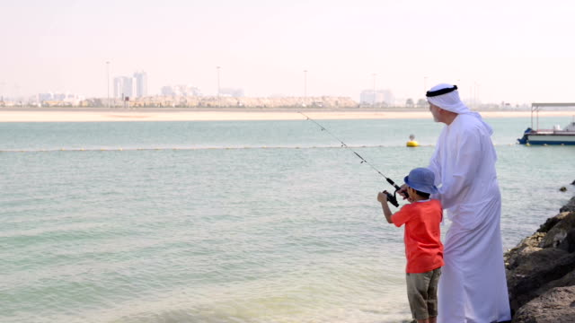 Emirati grandfather and little boy at fishing video
