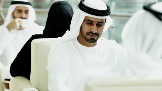 Emirati male female business executives meeting using tablets video
