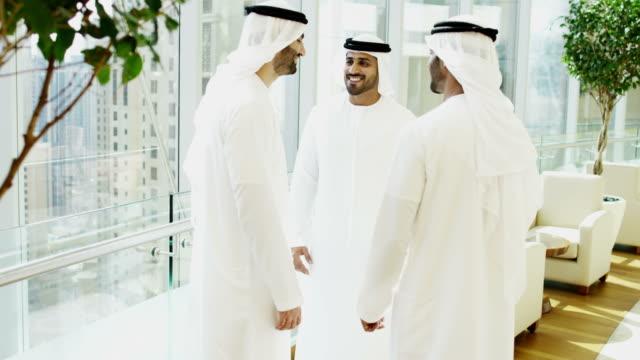 Emirati males in national kandura meeting shaking hands video