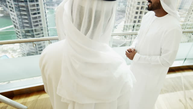 Emirati males national dress relaxing downtown hotel lobby video