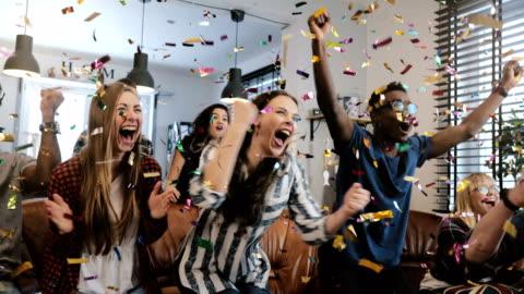 emotion. multi-ethnischen fans feiern sieg. konfetti 4k-slow-motion. leidenschaftliche fans schreien spiel im fernsehen beobachten - feiern stock-videos und b-roll-filmmaterial