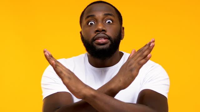 emocjonalne afro-amerykański mężczyzna przekraczania rąk, gest ostrzegawczy, żółte tło - negacja filmów i materiałów b-roll