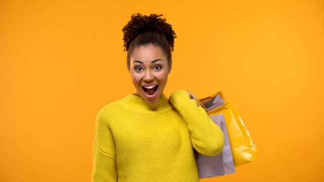 Emotional black lady holding bunch of dollars and shopping bags, cash back