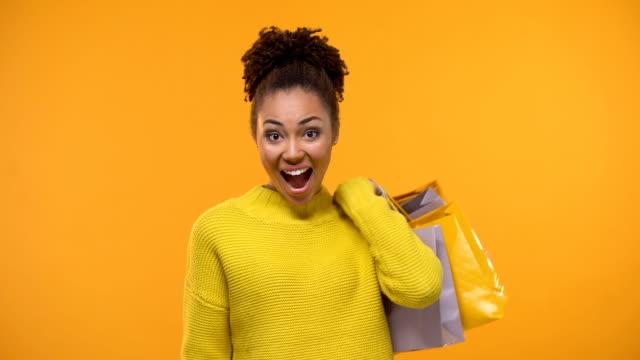 emocjonalna czarna dama trzymająca kilka dolarów i torby na zakupy, cash back - happy holidays filmów i materiałów b-roll