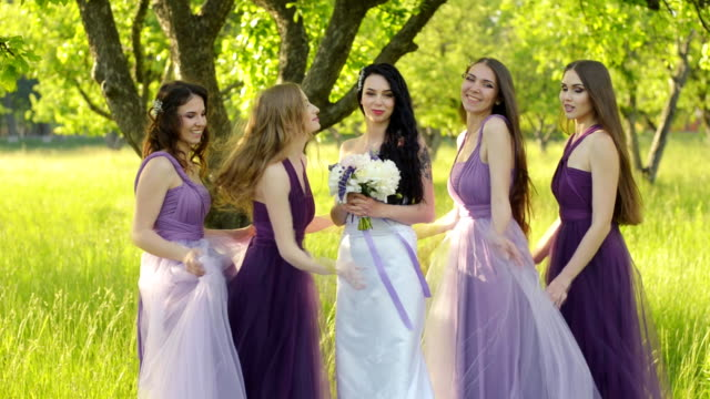 emotional bridesmaids hugging the bride. caucasian girls in purple wedding dresses smiling and posing outdoors. - wedding fashion stock videos and b-roll footage