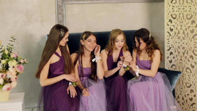 emotional bridesmaids look at the boutonniere on their hands, talking and laughing during the morning of the bride in a photo studio. girls in purple wedding dresses sitting on the studio couch. - wedding fashion stock videos and b-roll footage
