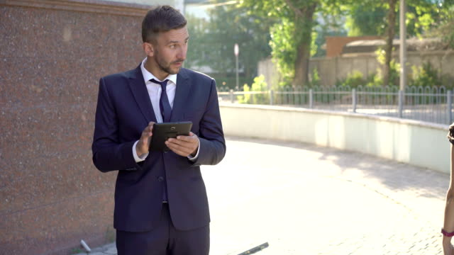stockvideo's en b-roll-footage met emotionele zakenman afgeleid van tablet op meisje uitgaan. fullhd - bewondering