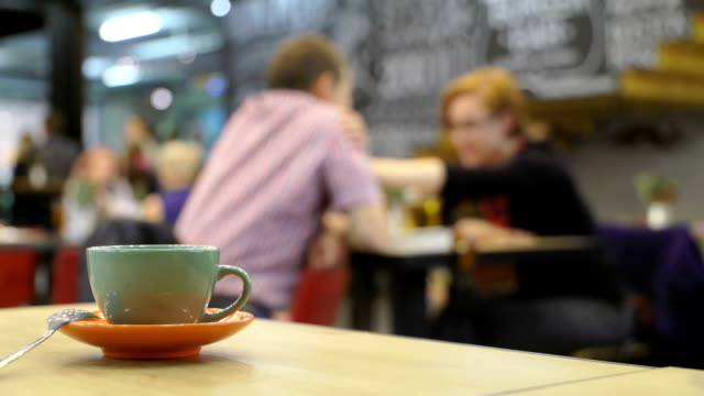 Emotional conversation, soothing woman's gesture. Cup of hot coffee espresso or tea on table in cafe on background of couple of beer drinkers in the blur. Olive cup on an orange saucer of hot beverage with Steam. love couple, husband and wife in a cafe video