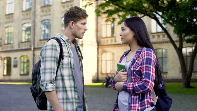 Emotional male student talking with ex-girlfriend near university, relationship video