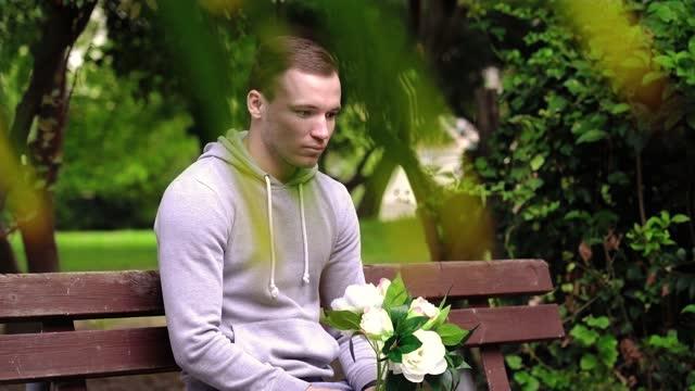 emocjonalny mężczyzna z białymi kwiatami czeka na randkę - data filmów i materiałów b-roll