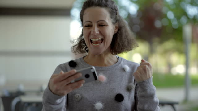 vídeos de stock, filmes e b-roll de mulher envelhecida média emocional que usa o smartphone ao ar livre. - plano médio