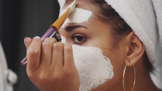 känslomässiga porträtt av en glad och lugn vacker naken flicka med en blå lera kosmetisk mask på halva hennes ansikte, titta på kameran spegeln tillämpa lera med en borste. - japanese bath woman bildbanksvideor och videomaterial från bakom kulisserna