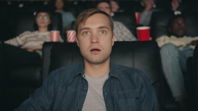 Emotional young man watching shocking film opening mouth in cinema