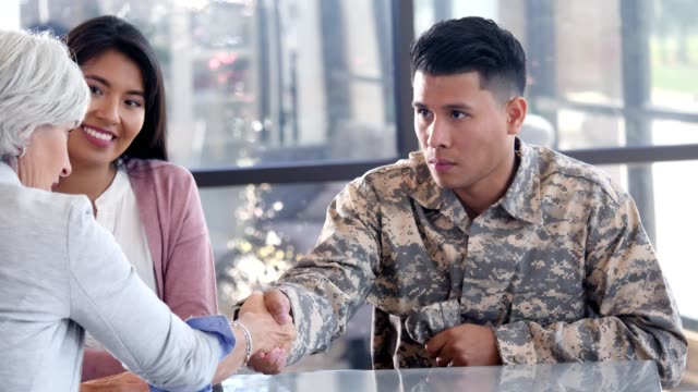 Emotionally distant military soldier solemnly greets a female mental health professional Uncertain male military soldier shakes a female counselor's hand in greeting. He looks at her with reluctance as she encourages him. His wife is sitting next to him. veteran stock videos & royalty-free footage